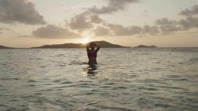 beautiful woman swimming in ocean then approaching beach at sunset / jamesby island, tobago cays, st. vincent and the grenadines - emergence stock videos & royalty-free footage