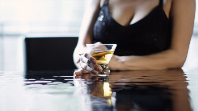 MS Beautiful woman swirling her drink while sitting at bar / Aspen, Colorado, United States