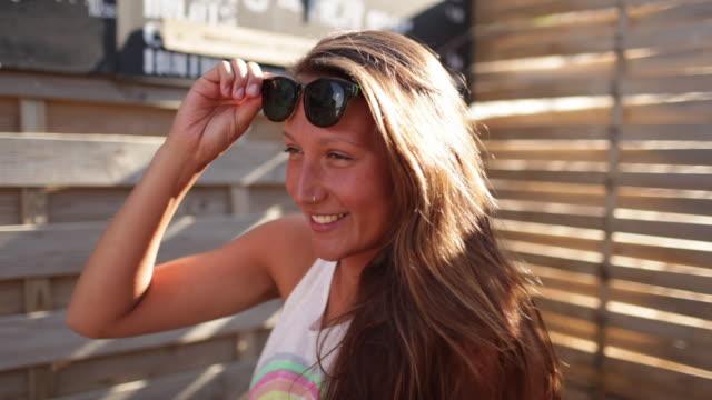 Beautiful woman taking off sunglasses, smiling at camera.