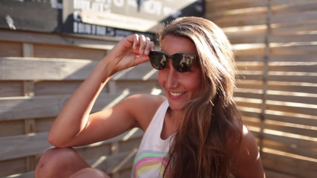 beautiful woman taking off sunglasses, smiling at camera. - sunglasses stock videos & royalty-free footage