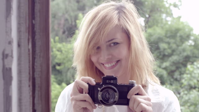 beautiful woman taking photos with retro camera - camera photographic equipment stock videos and b-roll footage