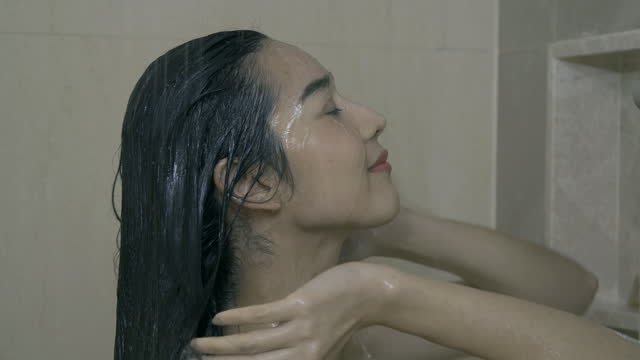 beautiful woman taking warm shower and rinsing out shampoo of her hair. - black hair stock videos & royalty-free footage