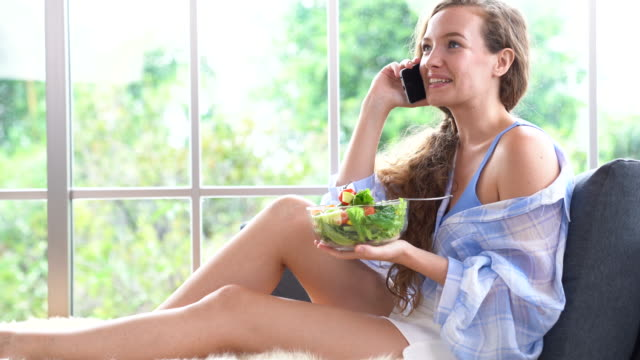 A beautiful woman talking on the phone while holding salad bowl on hand