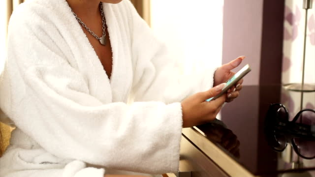 Beautiful woman texting in bathrobe