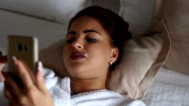 beautiful woman texting in bed - bathrobe stock videos & royalty-free footage