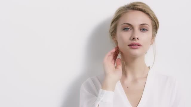vídeos de stock e filmes b-roll de beautiful woman touching hair against wall - mulher bonita