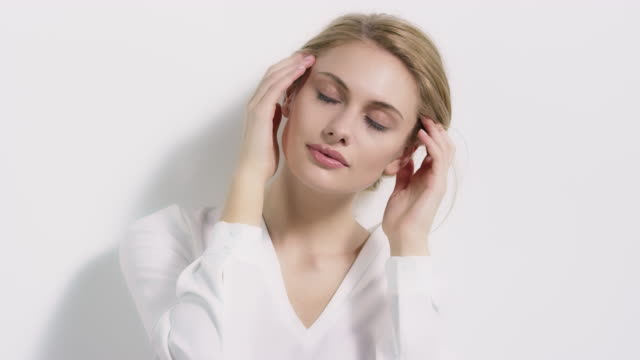 beautiful woman touching her face against wall - beauty treatment stock videos & royalty-free footage