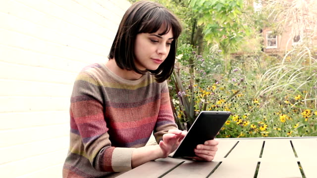 Beautiful woman using a tablet outdoors.