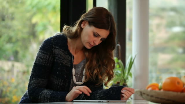 Beautiful woman using digital tablet at home.