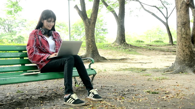 Beautiful woman using laptop computer in the park, smiling young woman sitting on the bench and typing computer in the park