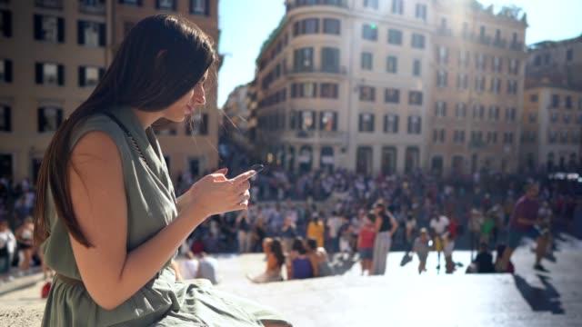vidéos et rushes de belle femme à l'aide de téléphone à la place d'espagne, rome - famous place