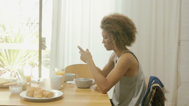stockvideo's en b-roll-footage met mooie vrouw met behulp van slimme telefoon aan ontbijttafel - eetkamer