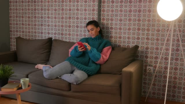 vídeos de stock e filmes b-roll de beautiful woman using smart phone at home - camisola