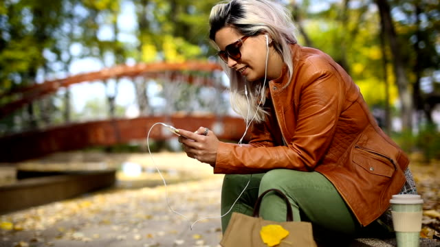 beautiful woman using smart phone in autumn park - autumn stock videos & royalty-free footage