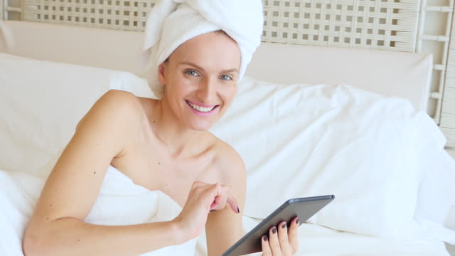 beautiful woman using tablet in bed - lying on side stock videos & royalty-free footage
