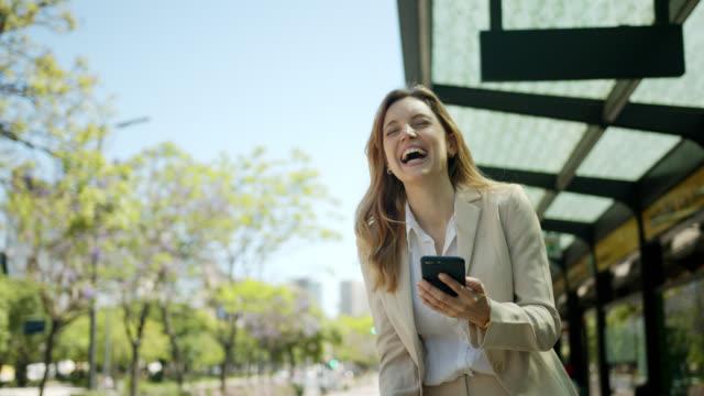 vídeos de stock, filmes e b-roll de a mulher bonita que espera a barra-ônibus ao ler algo engraçado no smartphone e beber toma o café - viagem de negócios