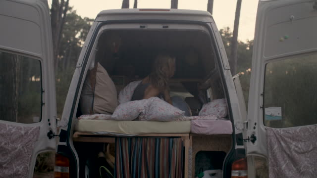 Beautiful woman waking up in her bed in a camper van in the forest in the South of France.