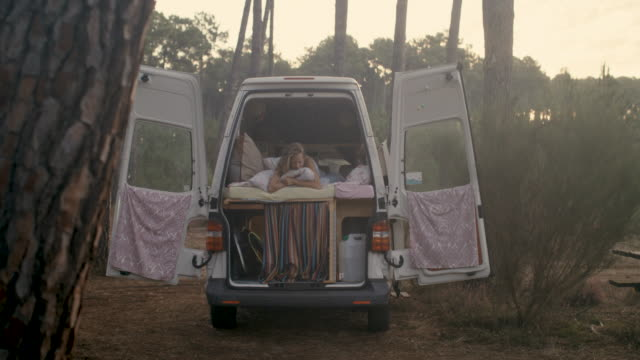 vidéos et rushes de beautiful woman waking up in her bed in a van with surfboards in the forest in the south of france. - équipement