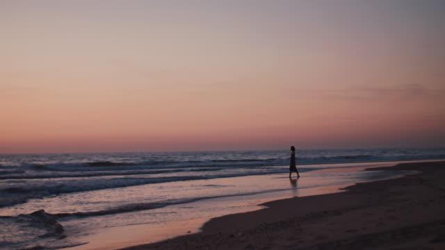 Beautiful woman walking at sunset on sandy beach at Atlantic coast in France