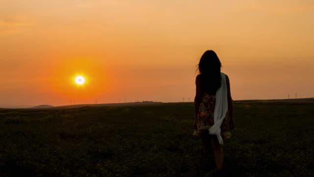 vidéos et rushes de belle femme marchant au coucher du soleil - plante sauvage