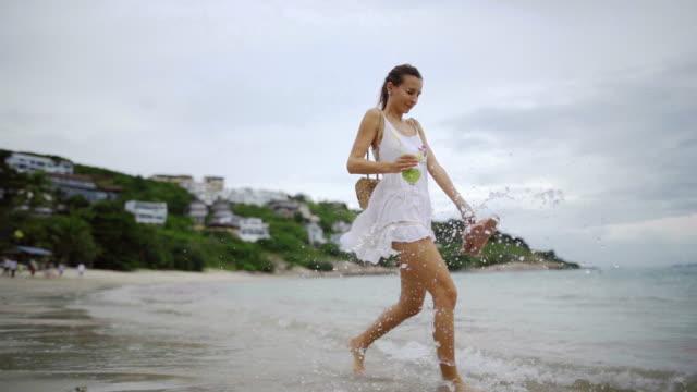 Beautiful woman walking on the beach in slow-mo