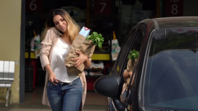 beautiful woman walking out of the supermarket holding her groceries in a paper bag while talking on phone and opening her car - entering stock videos & royalty-free footage