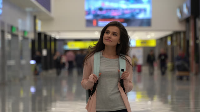 vidéos et rushes de belle femme marchant à travers l'aéroport regardant autour transportant le sac à dos attendant son vol - sac à dos