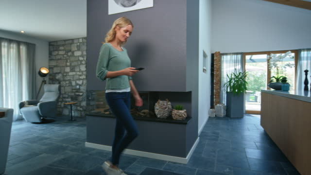 beautiful woman walking with smart phone at home - home interior stock videos & royalty-free footage