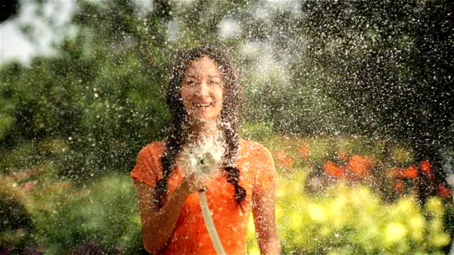 stockvideo's en b-roll-footage met beautiful woman watering in garden - formele tuin