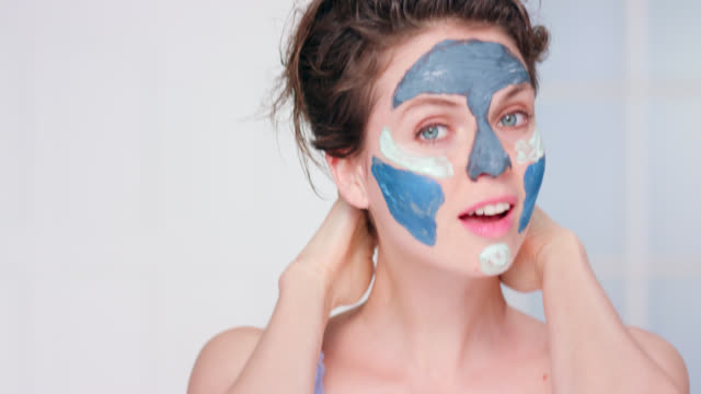 beautiful woman wearing a blue clay face mask. - color block stock videos and b-roll footage