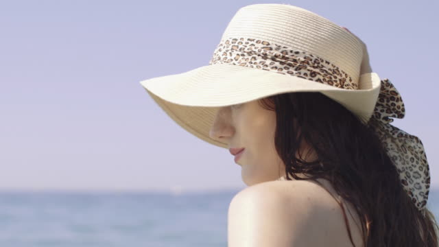stockvideo's en b-roll-footage met beautiful woman wearing a summer hat on the beach - hoed