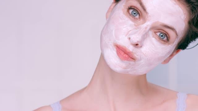 beautiful woman wearing a white moisturising face mask - フェイスパック点の映像素材/bロール