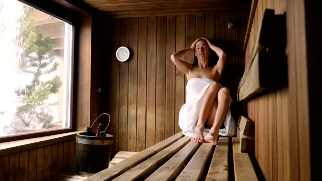 A beautiful woman wearing a white towel takes a sauna: The sauna is made of wood with a large window with a view of the snow.