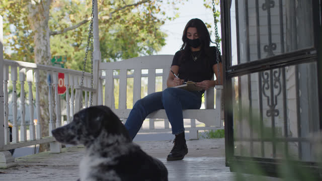 beautiful woman wearing face mask and writing in journal sits outdoors on porch with dog - diary stock videos & royalty-free footage