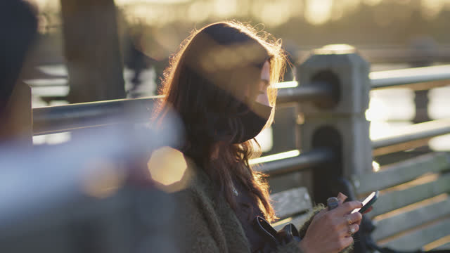 beautiful woman wearing protective face mask sits outdoors and uses smartphone - profile stock videos & royalty-free footage