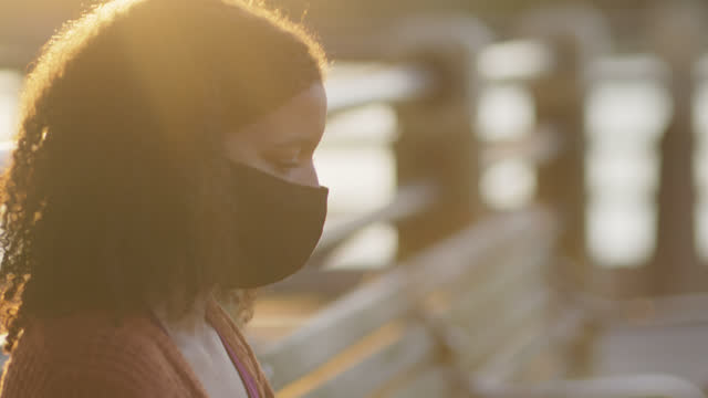 vidéos et rushes de cu beautiful woman wearing protective face mask uses laptop while sitting outdoors by waterfront - profil