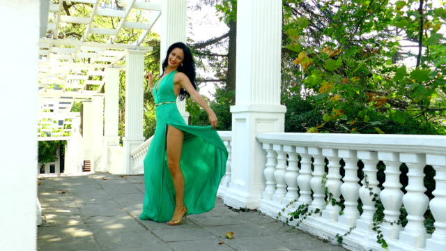 beautiful woman whirl among the columns in the park
