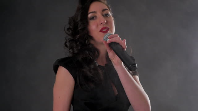 beautiful woman with a microphone sings on a black background