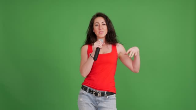 beautiful woman with a microphone sings on a green background - singing stock videos and b-roll footage