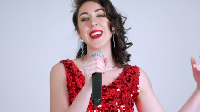 beautiful woman with a microphone sings on a white background - blouse stock videos & royalty-free footage