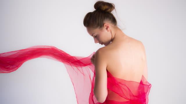 vídeos de stock, filmes e b-roll de mulher bonita com material de vermelho brilhante - cetim