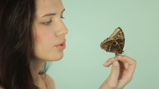 Schöne Frau mit Schmetterling auf Blau