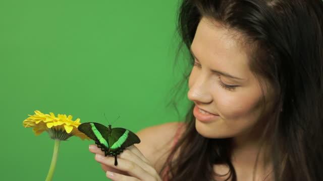 Schöne Frau mit Schmetterling im Grünen