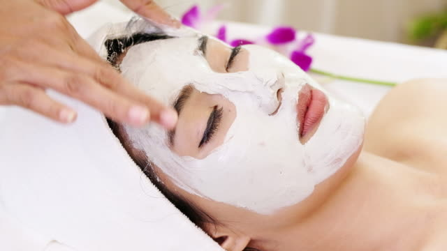 beautiful woman with facial mask at beauty salon.applying facial mask at woman face. - salone di bellezza video stock e b–roll