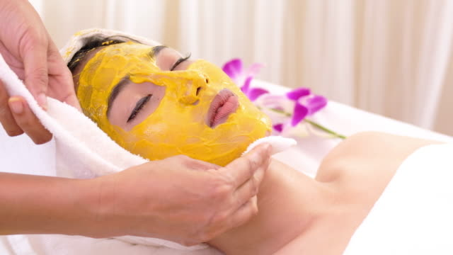 vídeos de stock e filmes b-roll de beautiful woman with facial mask at beauty salon.applying facial mask at woman face. - máscara facial