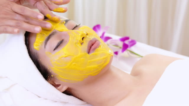 beautiful woman with facial mask at beauty salon.applying facial mask at woman face. - beauty treatment stock videos and b-roll footage