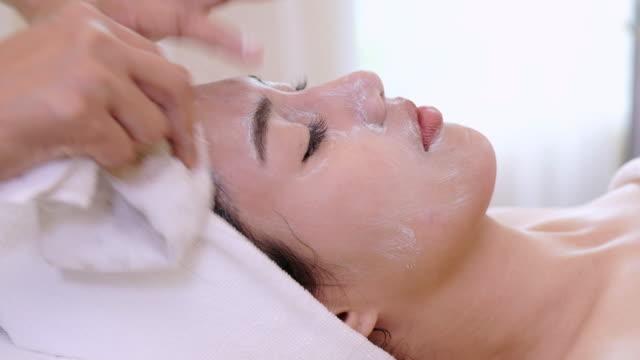 Beautiful woman with facial mask at beauty salon.Applying facial mask at woman face.