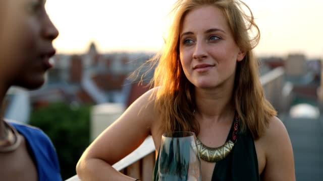 Schöne Frau mit Freundinnen auf dem Dach