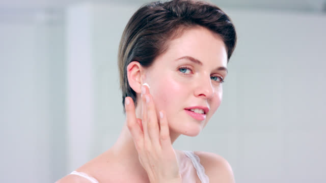 beautiful woman with fresh, clean skin and moisturising cream on her finger. - face cream stock videos and b-roll footage