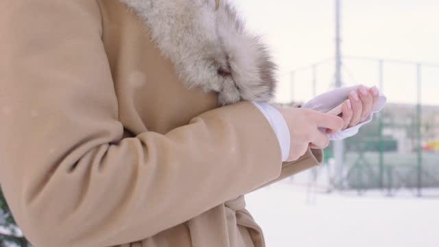 vidéos et rushes de belle femme avec le chapeau de fourrure utilisant le smartphone dans le stationnement d'hiver dans la ville pendant la journée par temps neigeux avec la neige tombante, le plan rapproché, le ralenti - manteau et blouson d'hiver